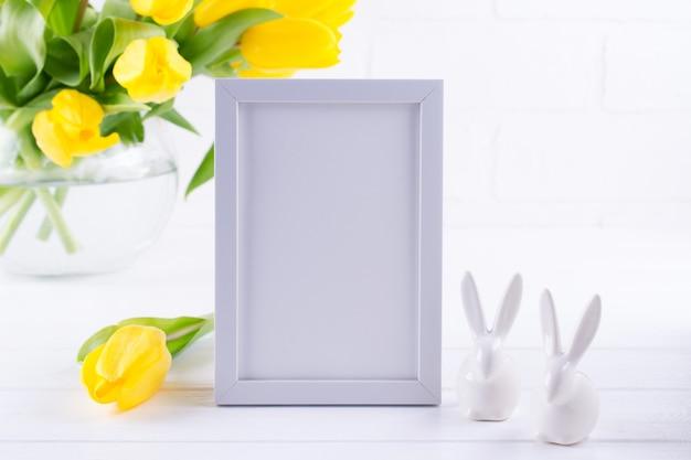 Modell des bilderrahmens verzierte gelbe tulpenblumen in der vase auf weißem hintergrund mit sauberem raum für text und design