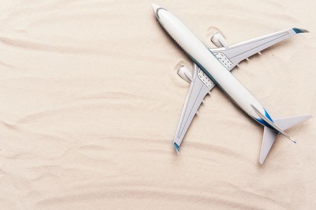 Modell des flugzeugs, flugzeug auf goldsandhintergrund. flaches lay-design. reise, urlaubskonzept