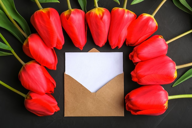 Modell des frischen roten tulpenblumenstraußes und der grußkarte im kraftpapierumschlag