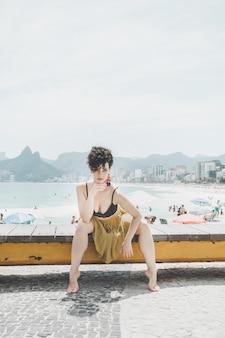 Modell des gelockten haares, das ein abendkleid trägt und auf der promenade in rio de janeiro aufwirft