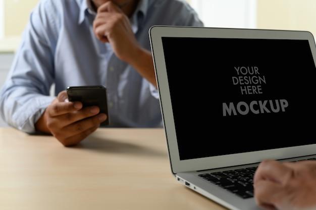Modell des geschäftsmannes unter verwendung des laptopschirmes