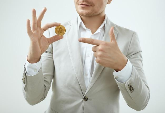 Modell des gutaussehenden mannes in einem grauen anzug der mode hält ein bitcoin