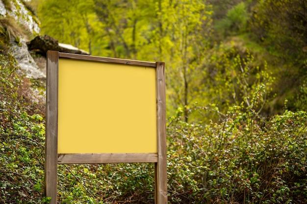 Modell des hölzernen zeichens in der natur mit vegetation im hintergrund nach regen.