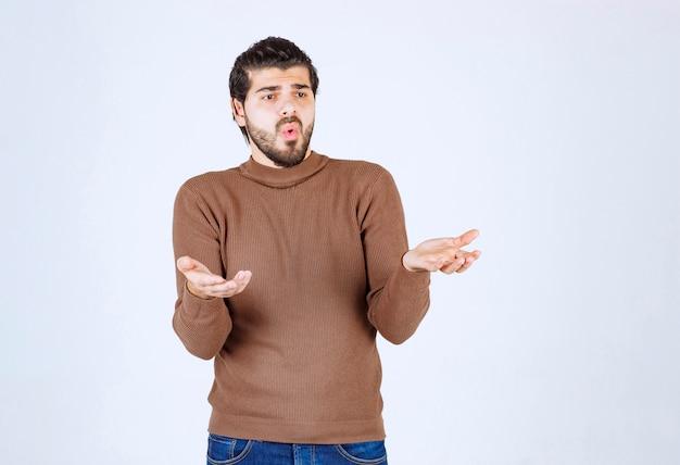 Modell des jungen attraktiven mannes, der hilflose geste mit arm und händen steht und zeigt. Kostenlose Fotos