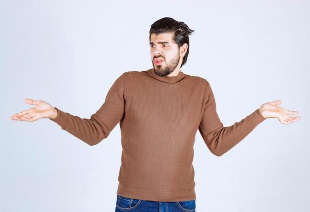 Modell des jungen attraktiven mannes, der hilflose geste mit arm und händen steht und zeigt.