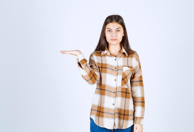 Modell des jungen mädchens im karierten hemd, das eine hand zeigt.