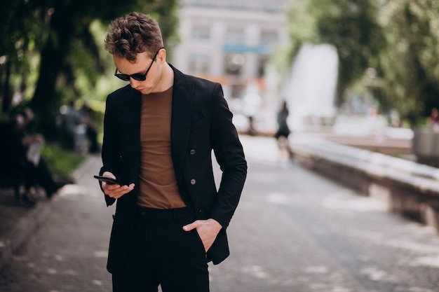Modell des jungen mannes, das telefon verwendet