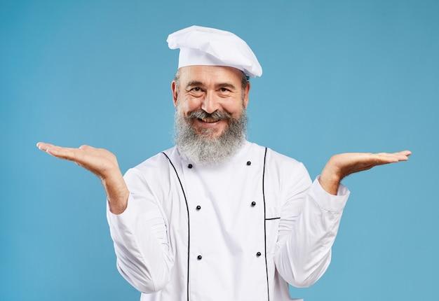 Modell des lächelnden küchenchefs, der auf blau präsentiert
