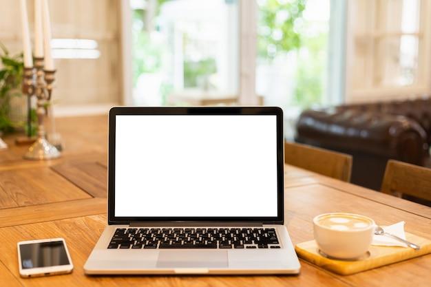 Modell des laptop-computers mit leerem bildschirm mit kaffeetasse und smartphone auf tabelle des kaffeehaushintergrunds, weißer bildschirm