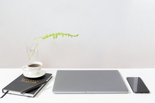 Modell des laptops mit kaffeetasse über notebooks und handy auf weißem tisch.