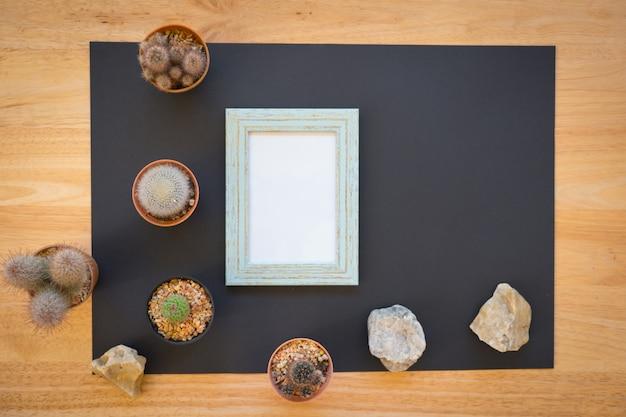 Modell des leeren fotorahmens mit kaktus auf hölzernem hintergrund