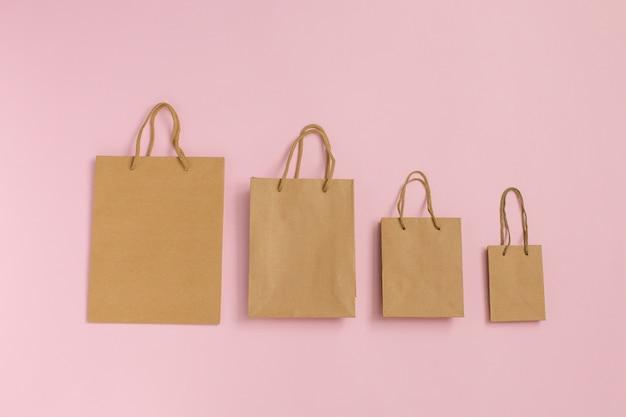 Modell des leeren handwerkspakets, modell von handwerkspapier-einkaufstaschen mit griffen auf rosa leeren braunen papiertragetaschen