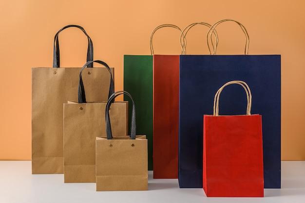 Modell des leeren handwerkspakets oder der bunten papiereinkaufstasche mit griffen