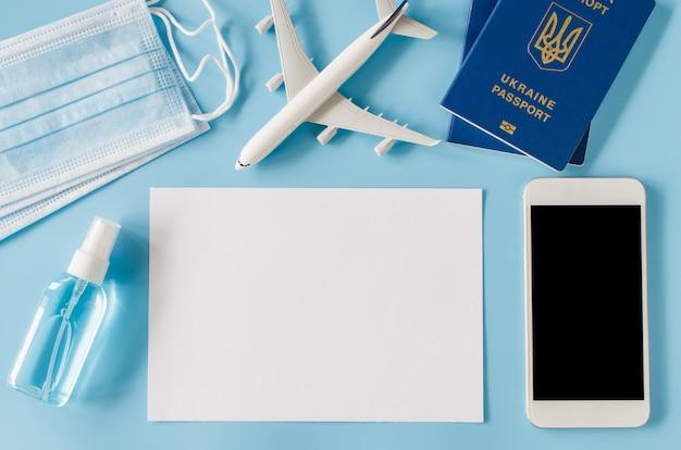 Modell des smartphones mit flugzeugmodell, pässen der ukraine, blatt papier, gesichtsmaske und händedesinfektionsspray