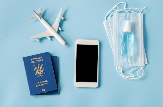 Modell des smartphones mit flugzeugmodell, pässen der ukraine, gesichtsmaske und händedesinfektionsspray