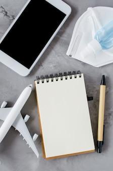 Modell des smartphones mit notebook, gesichtsmaske, gelflasche und flugzeugmodell