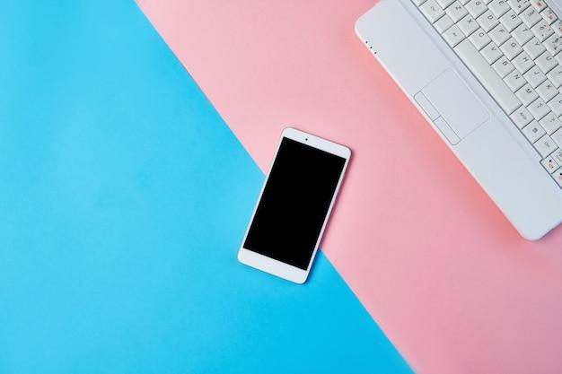 Modell-ebenenlagezusammensetzung mit smartphone und laptop auf einem blauen und rosa hintergrund.