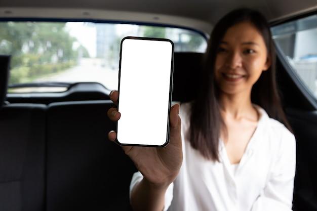 Modell einer asiatischen frau, die handy hält, während sie auf dem rücksitz des autos sitzt