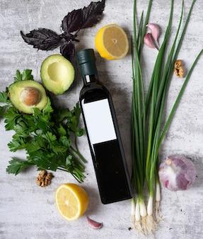 Modell einer flasche pflanzliches olivenöl auf hellem hintergrund mit gewürzkräutern und einem leeren etikett ...