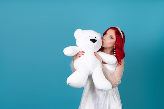Modell einer frau, die einen großen weißen teddybär umarmt und ihn auf die wange küsst