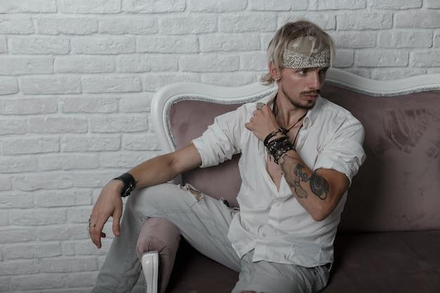 Modell eines attraktiven jungen mannes in modischer kleidung in einem stilvollen kopftuch mit tätowierung mit bart auf einem vintage-sofa