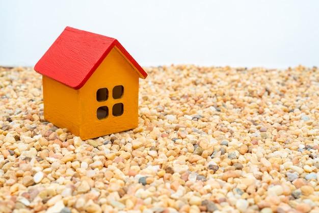 Modell eines gelben holzhauses mit rotem dach. vermietung und verkauf von gebäuden und ferienhäusern.