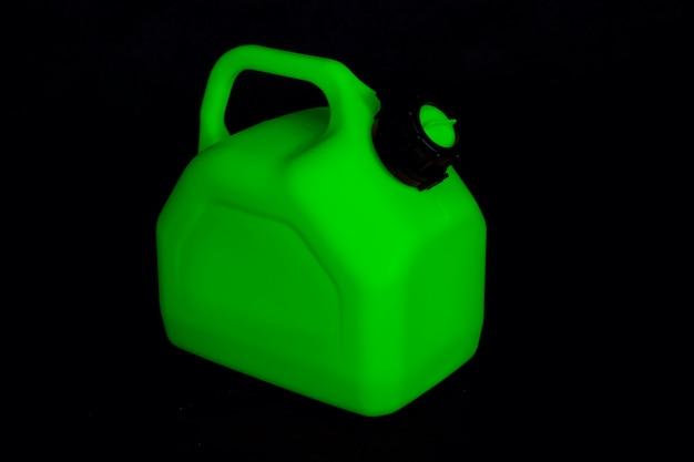 Modell eines grünen plastikkanisters für autokraftstoff auf schwarzem hintergrund. behälter für flüssigkeiten und gefährliche brennstoffe.