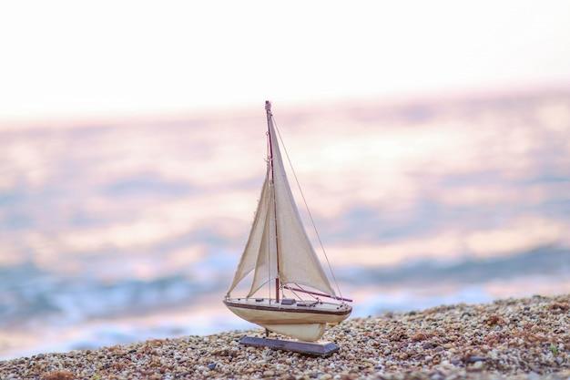 Modell eines hölzernen schiffs auf dem hintergrund einer natürlichen seeküste