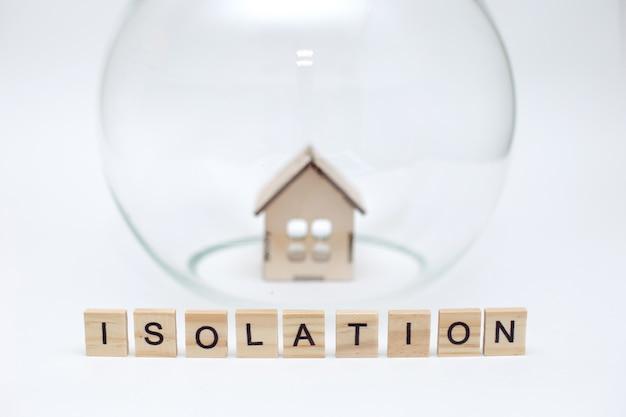 Modell eines holzhauses unter einer glaskuppel und holzbuchstaben mit der aufschrift isolation