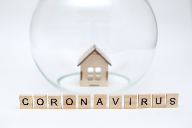 Modell eines holzhauses unter einer glaskuppel und holzbuchstaben mit der inschrift coronavirus