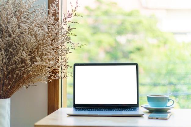Modell eines laptop-computers mit leerem bildschirm mit kaffeetasse und smartphone auf dem tisch des café-hintergrunds, weißer bildschirm