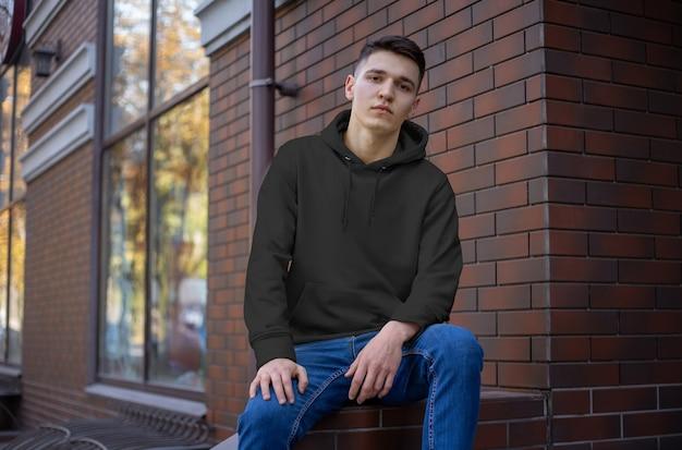 Modell eines leeren hoodies auf einem jungen mann in blue jeans, vorderansicht. vorlage schwarze haube für die werbung im online-shop. freizeitkleidung für design-präsentation.