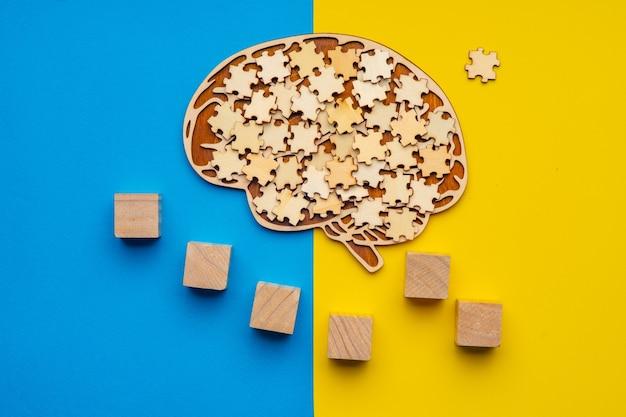 Modell eines menschlichen gehirns mit verstreuten puzzleteilen auf einem gelben und blauen hintergrund.