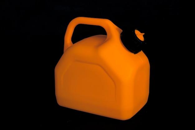 Modell eines orangefarbenen plastikkanisters für autokraftstoff auf schwarzem hintergrund. behälter für flüssigkeiten und gefährliche brennstoffe.