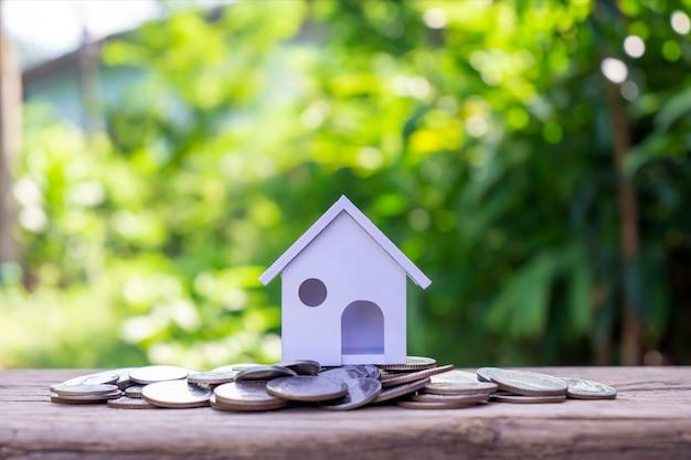 Modell eines scheinhauses auf einem haufen münzen und unscharfem natürlichen grünen hintergrund