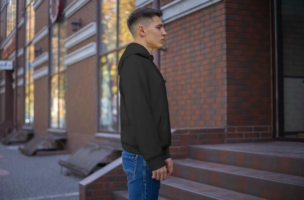 Modell eines schwarzen hoodies auf einem jungen mann in blue jeans, seitenansicht. vorlage für freizeitkleidung zur präsentation von design und muster. leere kapuze mit ärmeln für werbung im online-shop
