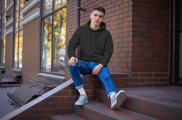 Modell eines schwarzen hoodies auf einem jungen mann, vorderansicht, präsentation auf der straße. eine vorlage für modische kleidung für die werbung im online-shop. langarm-kapuze für ihr design und muster