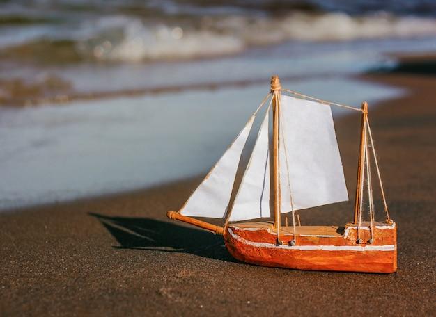 Modell eines segelschiffs aus holz, papier am ufer. kinderspielzeug, hobbys