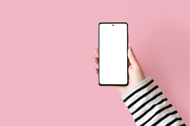 Modell eines smartphones in einer weiblichen hand auf einer rosa oberfläche