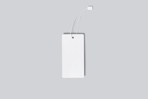 Modell eines vertikalen leeren weißen etiketts für kleidung auf grauem hintergrund. vorlage für ihr logo-design