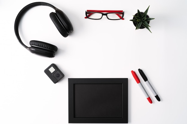 Modell, fotorahmen, actionkamera, kopfhörer, brille, stift und kaktus, rotes und schwarzes objekt auf weißem hintergrund