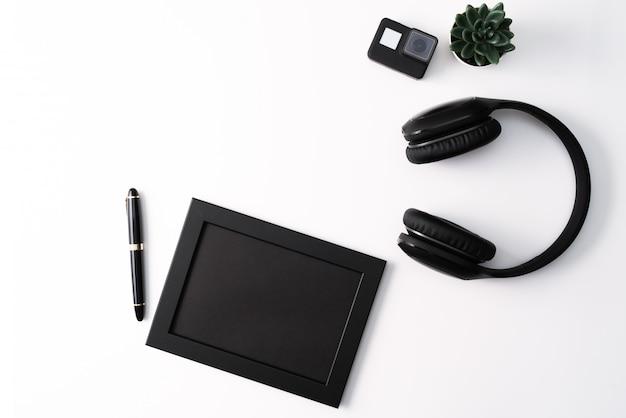 Modell, fotorahmen, aktionskamera, kopfhörer, stift und kaktus, schwarzer gegenstand auf weißem hintergrund