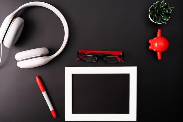 Modell, fotorahmen, kopfhörer, brille, stift und kaktus