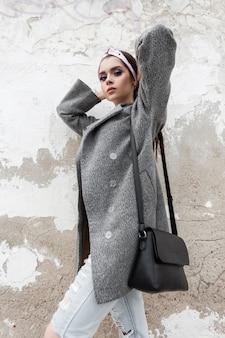 Modell glamour junge frau im grauen eleganten mantel im glamourösen bandana mit stilvoller handtasche entspannt sich in der nähe der weißen vintage-wand auf der straße. schönes mädchen in lässiger oberbekleidung genießt den frühlingstag im freien.