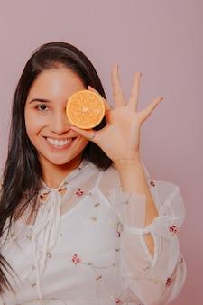 Modell hält eine orange.