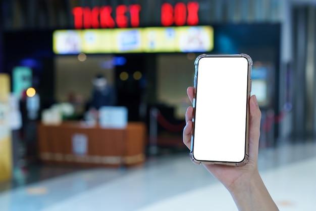 Modell, hände, die leeres handy mit weißem bildschirm im verschwommenen kino halten, digitales zahlungskonzept