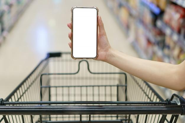 Modell, hände, die leeres weißes bildschirmhandy mit einkaufswagen im supermarkt halten