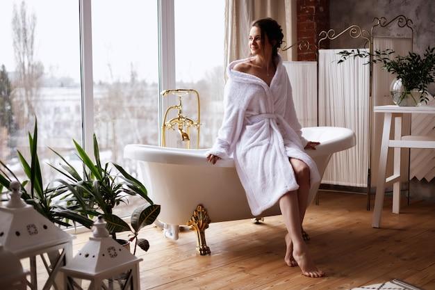 Modell im bademantel sitzt auf einer badewanne