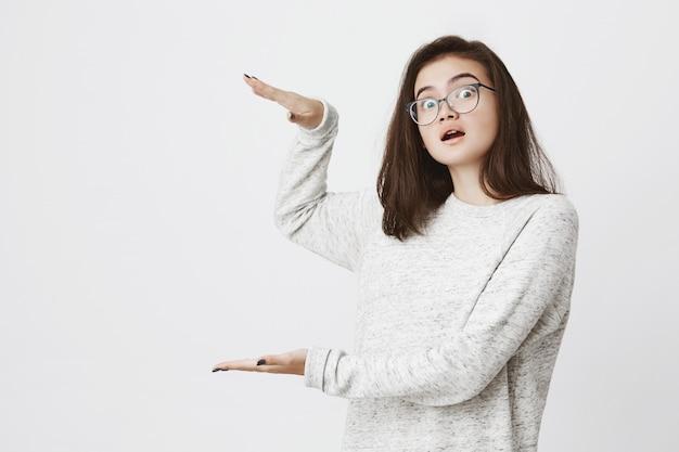 Modell in brille, die etwas großes zeigt, indem sie hände hält und dabei erstaunt und überrascht aussieht.