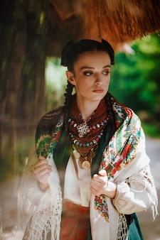Modell in einem ukrainischen kleid wirft im park auf